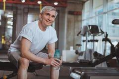 Hombre mayor que se resuelve en el gimnasio fotos de archivo