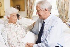 Hombre mayor que se sienta con su esposa en hospital imagen de archivo libre de regalías