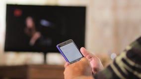 Hombre mayor que se sienta con un teléfono en una silla de cuero cerca de la casa TV SMS que mecanografía del hombre y foto de ob metrajes