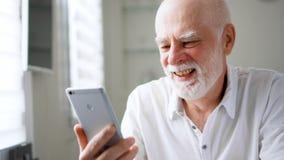 Hombre mayor que se sienta en casa con smartphone El hablar usando el mensajero móvil app Mano que agita sonriente almacen de video