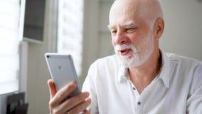 Hombre mayor que se sienta en casa con smartphone Usando hablar móvil vía el mensajero app Mano que agita sonriente en el saludo metrajes