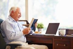 Hombre mayor que se sienta en el escritorio que mira el marco de la foto Fotos de archivo libres de regalías