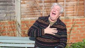Hombre mayor que se sienta en el jardín y la risa metrajes