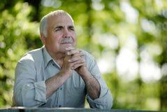 Hombre mayor que se sienta en el pensamiento del jardín Fotos de archivo