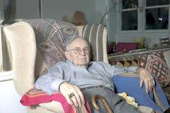 Hombre mayor que se sienta en el sofá Imágenes de archivo libres de regalías