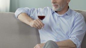 Hombre mayor que se sienta en el sofá con el vidrio de vino, disfrutando del momento, lagar privado almacen de video
