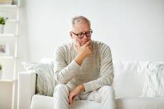 hombre mayor que se sienta en el sofá en casa y el pensamiento Imagen de archivo libre de regalías