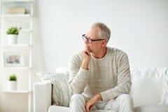 hombre mayor que se sienta en el sofá en casa y el pensamiento Fotografía de archivo libre de regalías
