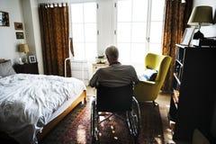 Hombre mayor que se sienta en la silla de ruedas solamente foto de archivo libre de regalías