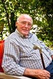 Hombre mayor que se sienta en su jardín Foto de archivo libre de regalías