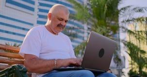 Hombre mayor que se sienta en un banco de parque entre las palmeras y que mira la pantalla del ordenador portátil almacen de video