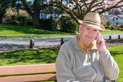 Hombre mayor que habla en el teléfono celular en parque Fotos de archivo libres de regalías