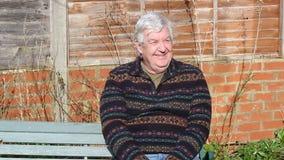 Hombre mayor que se sienta en un banco y agitar almacen de metraje de vídeo