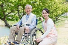 Hombre mayor que se sienta en una silla de ruedas con el cuidador Foto de archivo