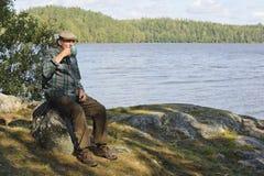 Hombre mayor que se sienta por un lago Imágenes de archivo libres de regalías