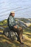Hombre mayor que se sienta por un lago Fotos de archivo