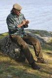 Hombre mayor que se sienta por un lago Foto de archivo libre de regalías