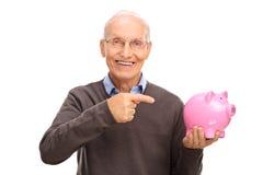 Hombre mayor que se sostiene y que señala hacia un piggybank Fotografía de archivo