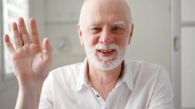 Hombre mayor que sienta en casa hablar vía el mensajero app Skype Mano que agita sonriente en el saludo almacen de metraje de vídeo