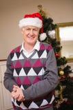 Hombre mayor que sonríe al lado del árbol de navidad Foto de archivo