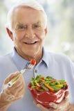 Hombre mayor que sonríe en la cámara y que come la ensalada Imágenes de archivo libres de regalías