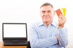 Hombre mayor que sonríe y que muestra la tarjeta de crédito Imagen de archivo