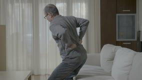 Hombre mayor que sostiene con las manos el suyo sensación trasera de dolor mal porque dolor del riñón - metrajes