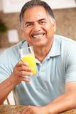 Hombre mayor que sostiene el zumo de naranja Imágenes de archivo libres de regalías