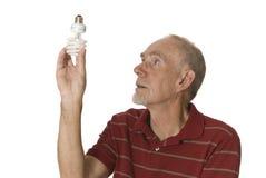Hombre mayor que sostiene la bombilla de poca energía Imagen de archivo libre de regalías