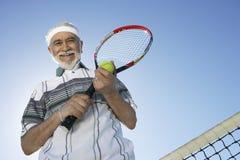 Hombre mayor que sostiene la estafa y la bola de tenis Imagenes de archivo