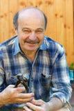 Hombre mayor que sostiene pares de alicates en su mano Imagenes de archivo