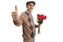 Hombre mayor que sostiene un manojo de rosas rojas que muestran los pulgares para arriba fotos de archivo libres de regalías