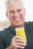 Hombre mayor que sostiene un vidrio de zumo de naranja fresco Foto de archivo