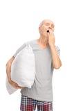 Hombre mayor que sostiene una almohada y que bosteza Imagenes de archivo