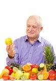 Hombre mayor que sostiene una manzana verde Foto de archivo libre de regalías