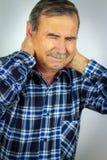 Hombre mayor que sufre con dolor de cuello severo Fotos de archivo