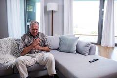 Hombre mayor que sufre de ataque del corazón imagen de archivo libre de regalías