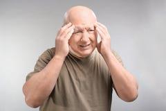 Hombre mayor que sufre de dolor de cabeza en fondo ligero Foto de archivo libre de regalías