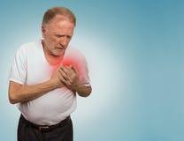 Hombre mayor que sufre de mún dolor en su pecho imagenes de archivo