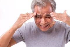 Hombre mayor que sufre del dolor de cabeza, tensión, jaqueca Imagenes de archivo