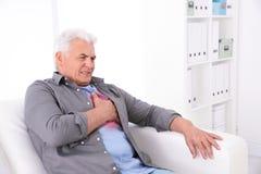 Hombre mayor que tiene ataque del corazón imagenes de archivo