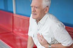 Hombre mayor que tiene ataque del corazón imagen de archivo libre de regalías