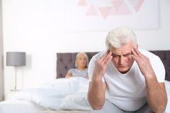Hombre mayor que tiene conflicto con su esposa en dormitorio fotos de archivo