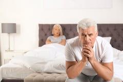 Hombre mayor que tiene conflicto con su esposa en dormitorio foto de archivo libre de regalías