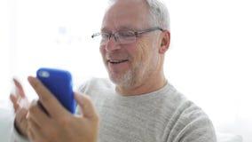 Hombre mayor que tiene llamada video en el smartphone en casa 126 almacen de video