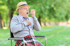 Hombre mayor que tiene un ataque de asma en parque imagenes de archivo