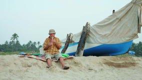 Hombre mayor que toca la flauta de bambú en la playa al lado del barco de pesca metrajes