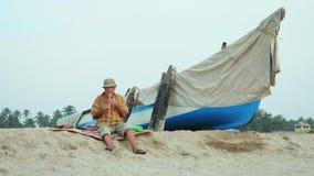 Hombre mayor que toca la flauta de bambú en la playa al lado del barco de pesca almacen de metraje de vídeo