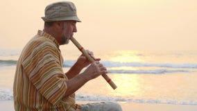 Hombre mayor que toca la flauta de bambú en la playa en la puesta del sol almacen de metraje de vídeo
