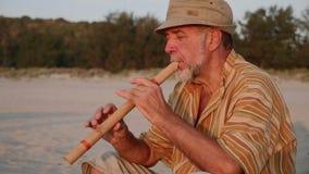 Hombre mayor que toca la flauta de bambú en la playa en la puesta del sol metrajes
